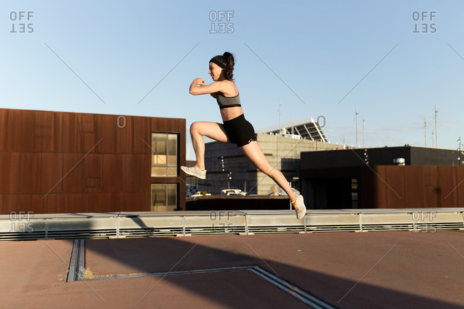 Side view of young runner woman sprint and jumping on the streets of Barcelona in a sunset of summer