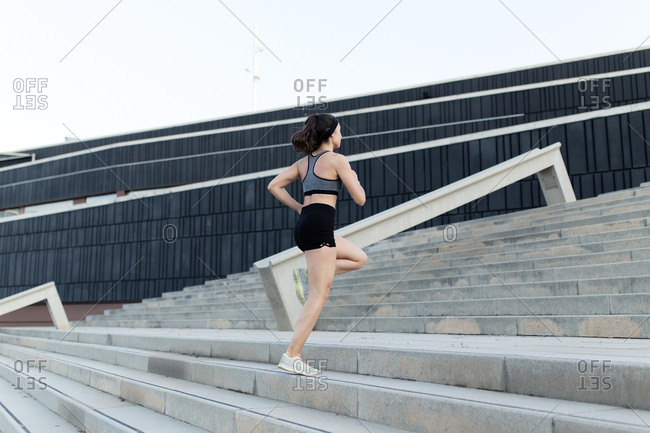 Young runner woman training climbing stairs on the streets of Barcelona in afternoon