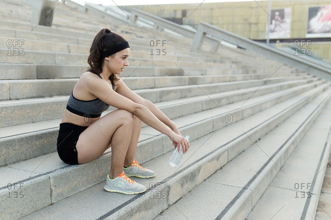 Young woman sitting and relaxing on the stairs of the city of Barcelona and drinking water after workout