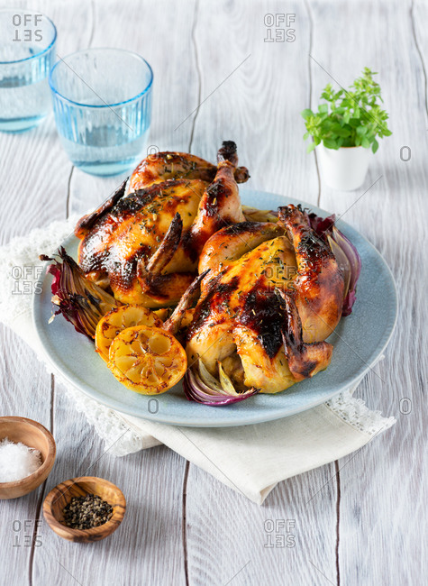 Homemade roasted cornish hens with lemon and onions on blue plate over wooden background