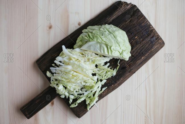 Raw fresh sliced cabbage on dark wooden cutting board