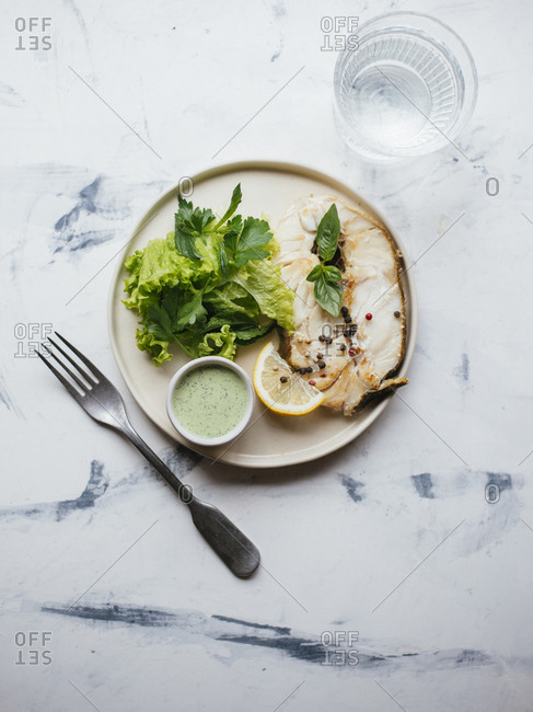 Fried codfish steak served with green leaf salad and sour cream basil salsa