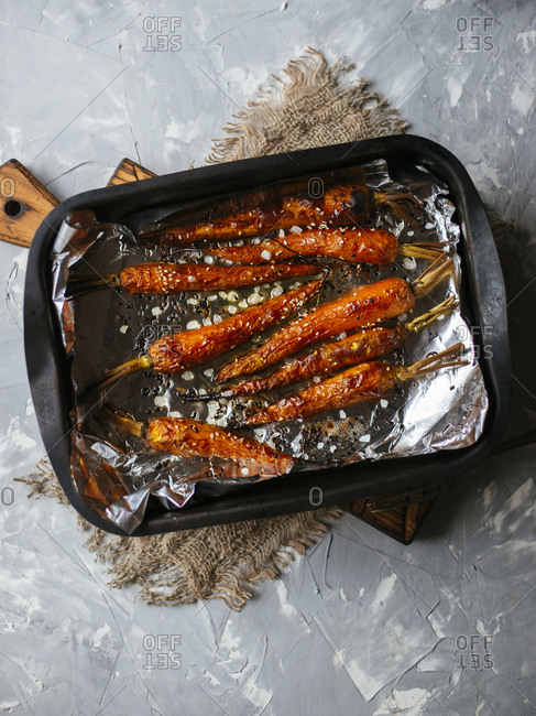 Roasted carrots with sesame seeds and sea salt on a tray