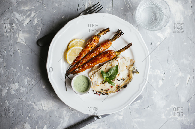 Fried codfish steak served with roasted carrot and sour cream basil salsa