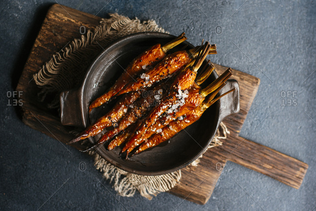 Roasted carrots with sesame seeds and sea salt in dark ceramic bowl overhead view