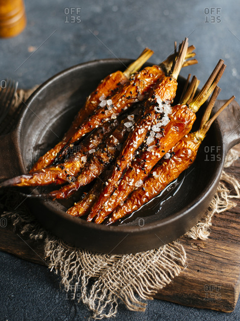Roasted carrots with sesame seeds and sea salt in dark ceramic bowl