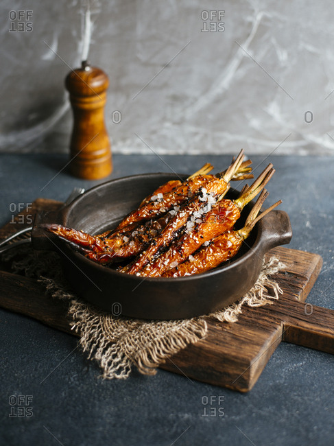 Roasted carrots with sesame seeds, olive oil and sea salt in dark ceramic bowl