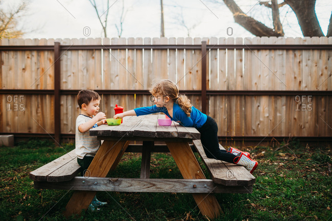 Girl reaching into brother's snack bowl on backyard picnic table