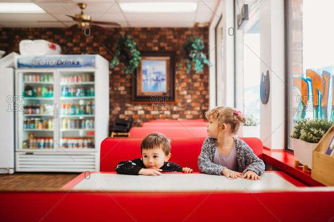 Kids sitting in red diner booth