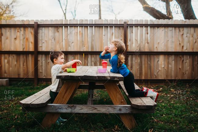 Kids eating snacks on backyard picnic table