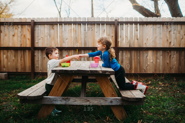 Boy sharing snack with sister on backyard picnic table