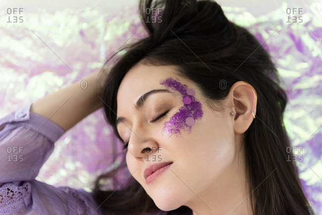 Woman with purple glitter on cheek