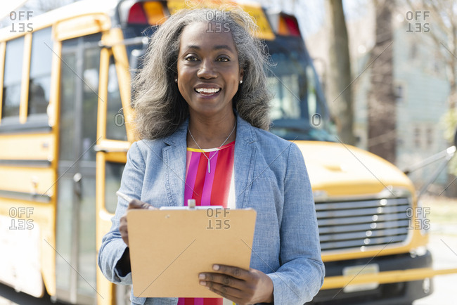 Smiling teacher with clipboard by school bus