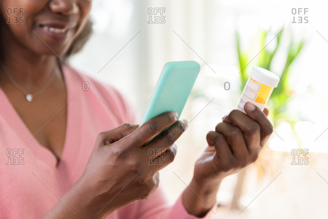 Mature woman holding smart phone and medicine bottle