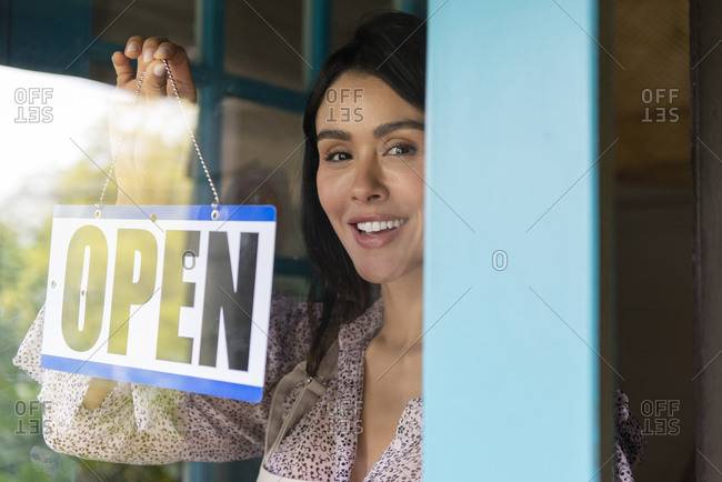Woman turning open sign in shop window