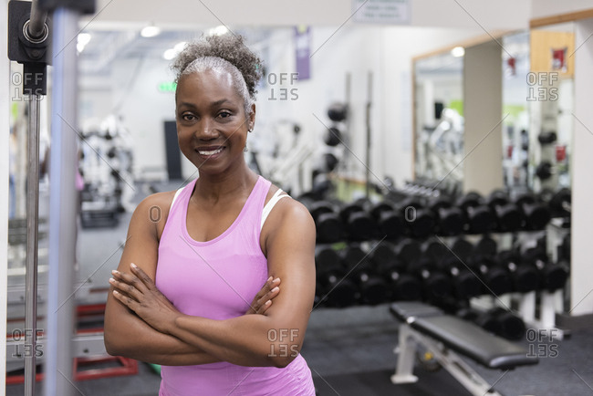 Smiling mature woman with arms crossed in gym