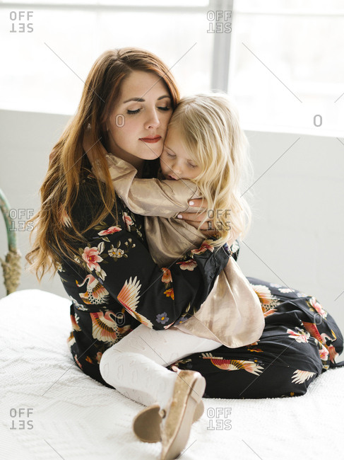 Mother comforting her daughter on bed