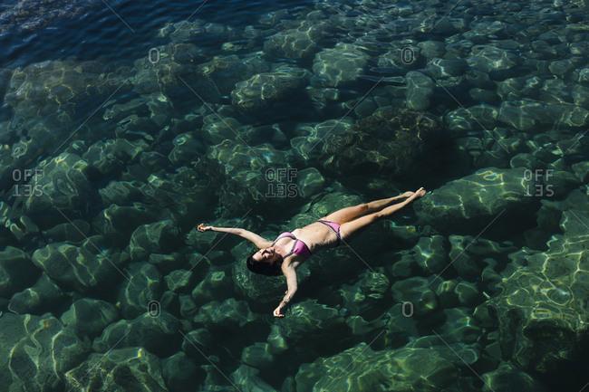 Woman in bikini swimming in sea