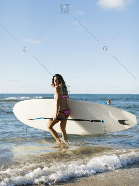 Woman with paddleboard and oar on beach