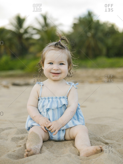 Baby girl wearing blue dress sitting on beach