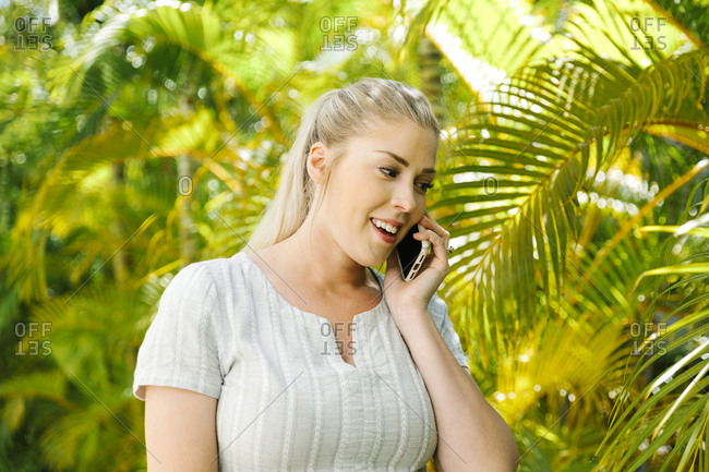 Woman talking on smart phone by palm trees