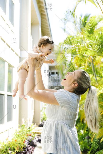 Woman lifting baby daughter