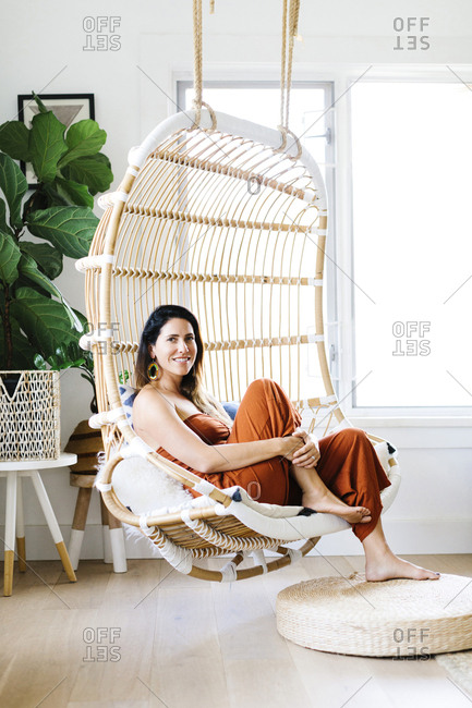 Mid adult woman sitting on hanging chair