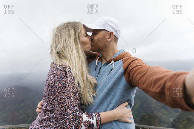 Mid adult couple taking selfie while kissing