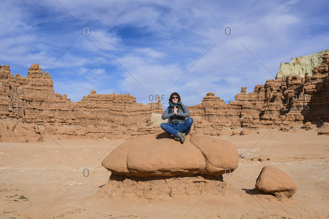 Woman meditating on rock in Goblin Valley State Park, Utah, USA