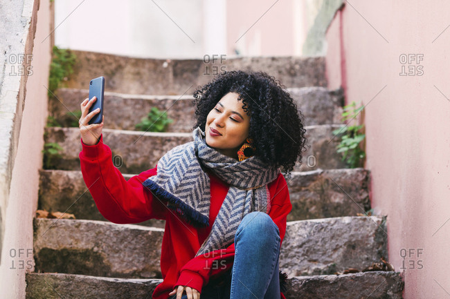 Young woman taking selfie on steps