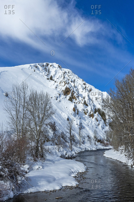 River by bare trees in snow in Sun Valley, Idaho, USA