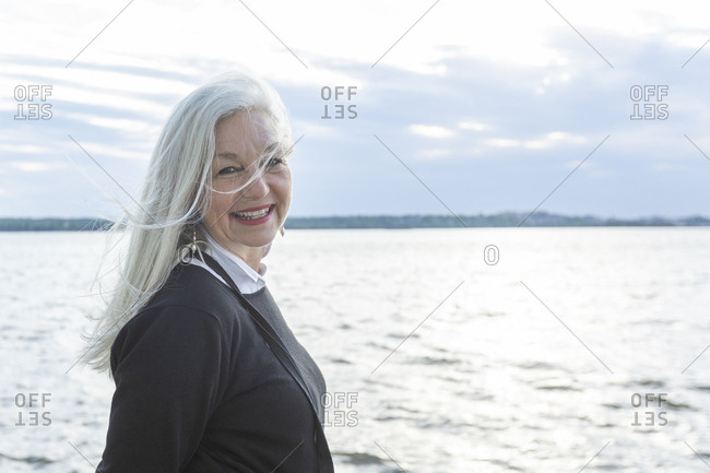 Smiling mature woman by Potomac River in Washington DC, USA