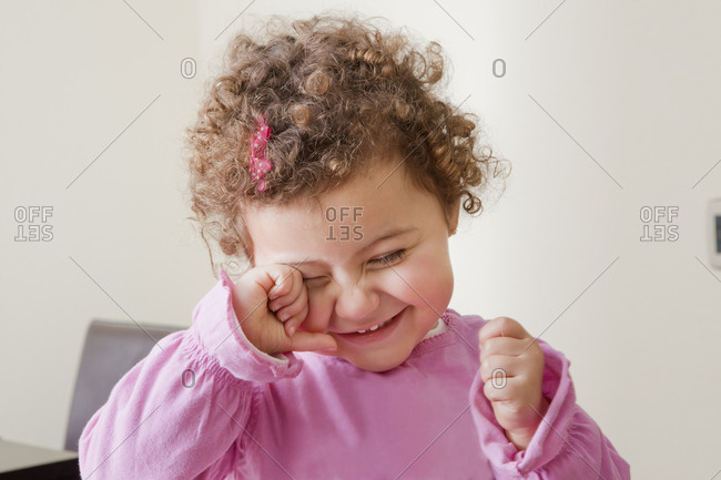 Smiling girl rubbing her eye