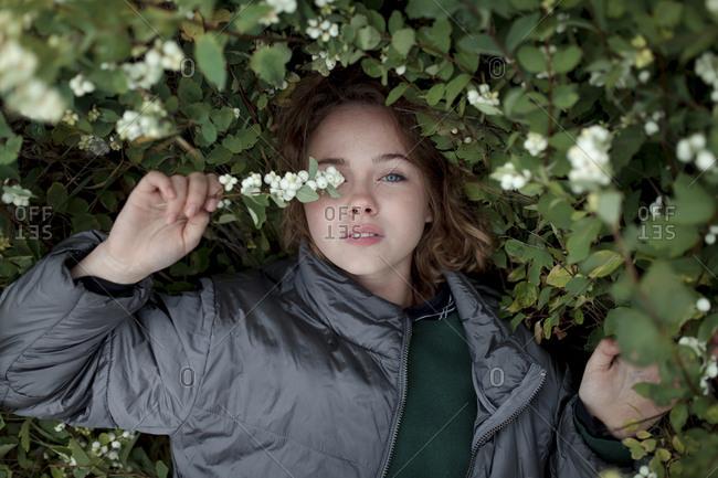 Teenage girl in bush with flowers