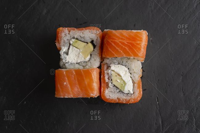 Salmon sushi on black surface