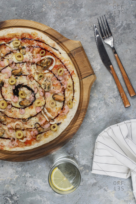 Pizza topped with olives and swirl of sauce