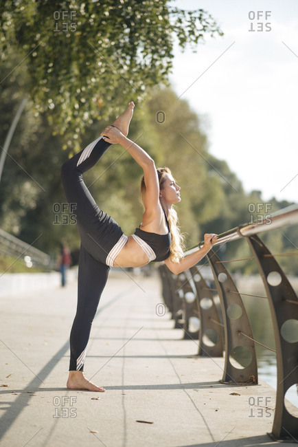 Young woman practicing yoga on footpath