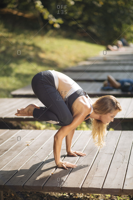 Young woman practicing yoga on boardwalk