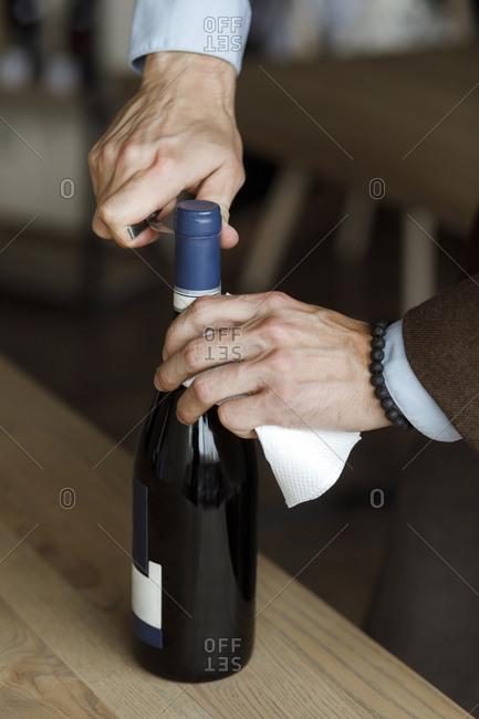 Hands of man opening bottle of wine