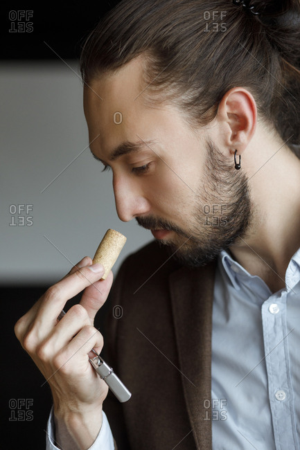 Young man smelling wine on cork at tasting