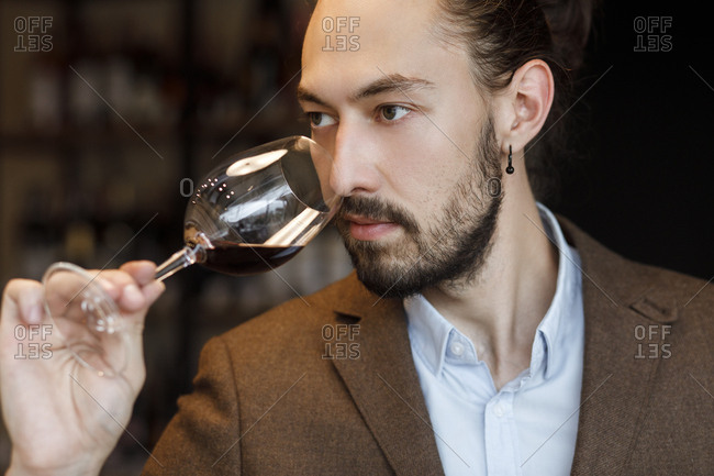 Young man smelling wine in glass at tasting