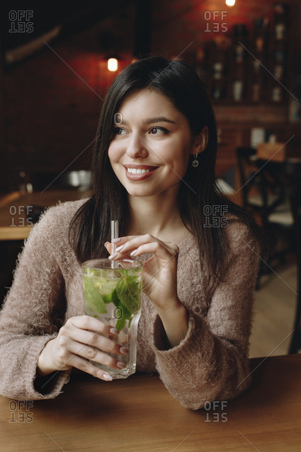 Woman holding straw in cocktail with mint leaves