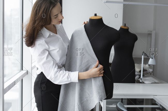 Fashion designer working with dressmaker's model in studio