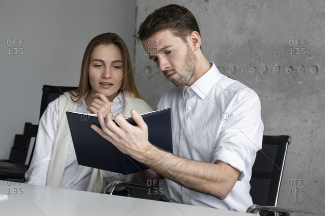 Businessman showing notebook to colleague