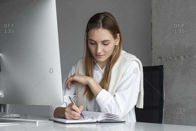 Businesswoman writing in notebook