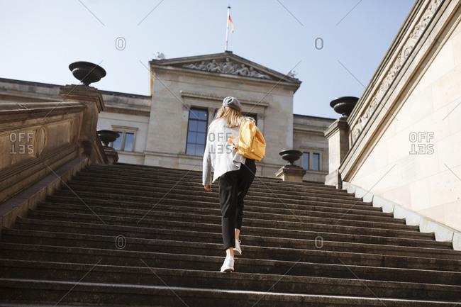 Young woman walking on steps in Berlin, Germany