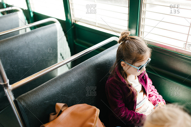 Young girl on bus with sunglasses