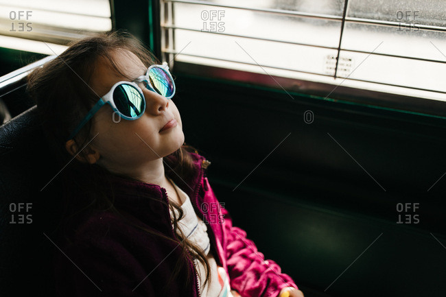 Little girl on bus with sunglasses