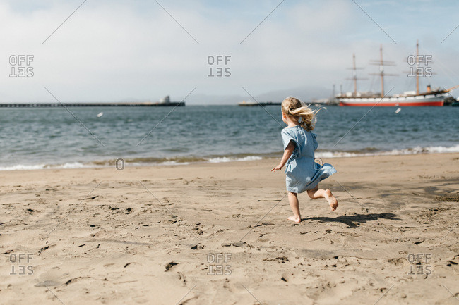 Little girl playing at aquatic park with ship in the background