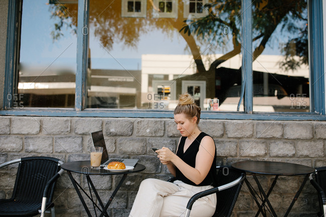 Young professional woman working remotely from an outdoor coffee shop
